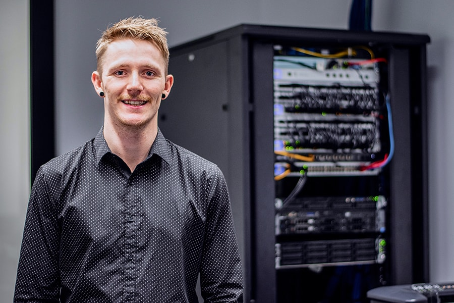 Brodie guy in button up collared shirt with office server behind him