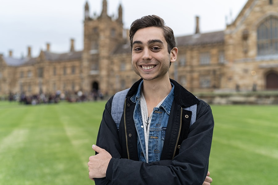 Danny boy in casual wear smiling with university building and courtyard behind him