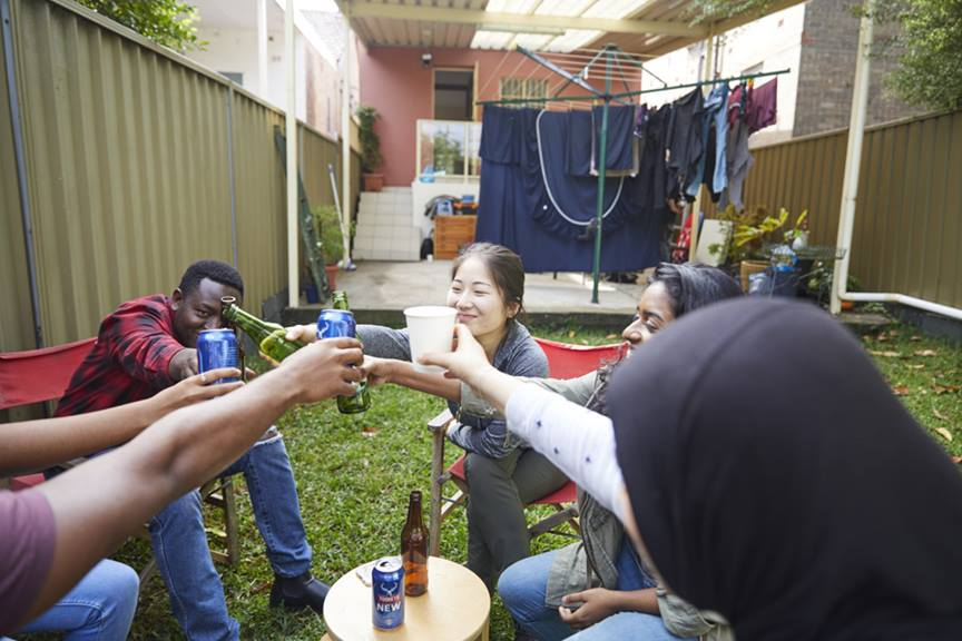 Group of young people cheers drinks