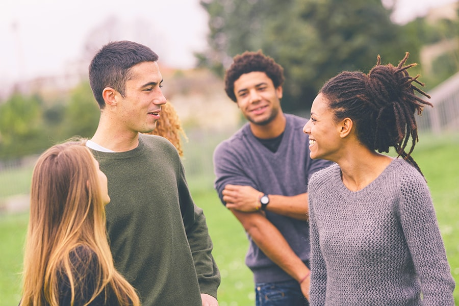 group of young people smiling and talking in park