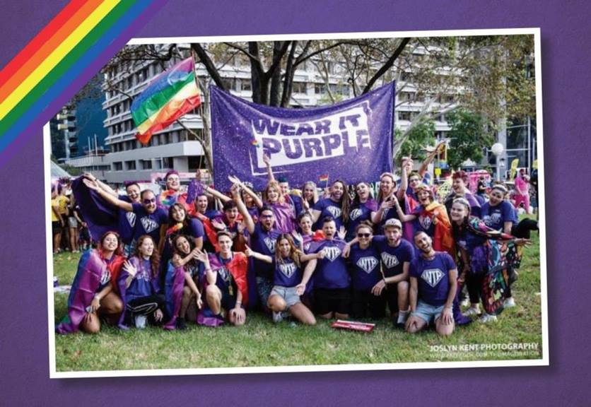 group of young people wearing purple shirts with a wear it purple banner and rainbow flag flying beh