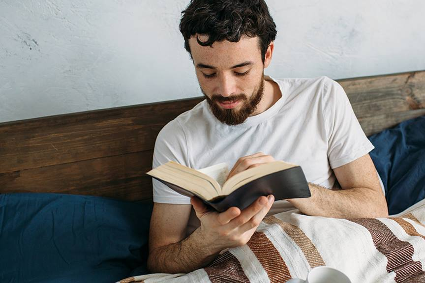 guy reading in bed with a mug feature