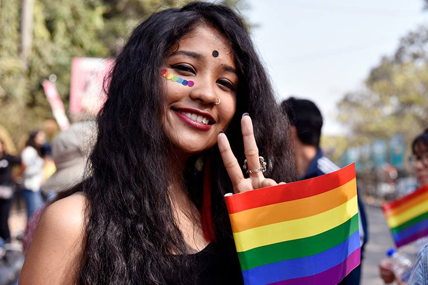 Indian girl smiling at the camera holding rainbow flag and peace sign with her fingers parade behind