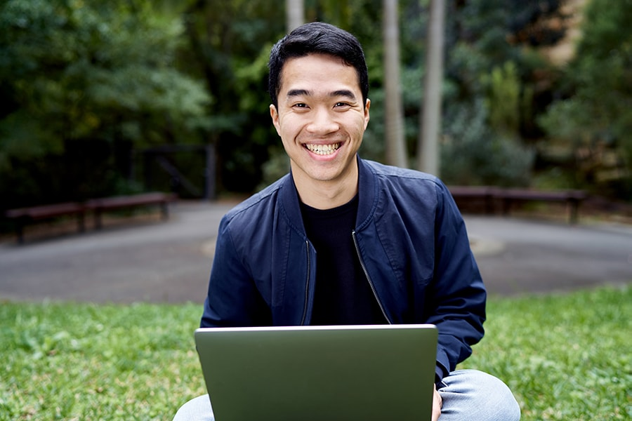 Kwan guy smiling holding laptop sitting on grass
