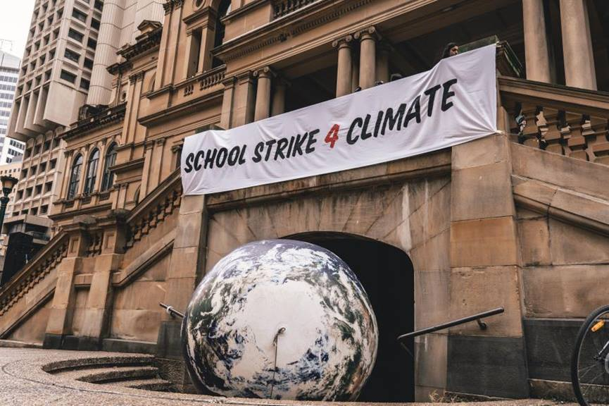 school strike 4 climate change sign above world globe