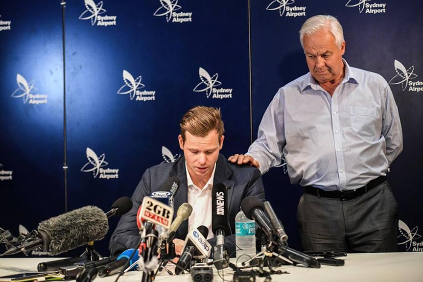 steve smith cricketer looking down speaking into microphones with man next to him with his hand on s