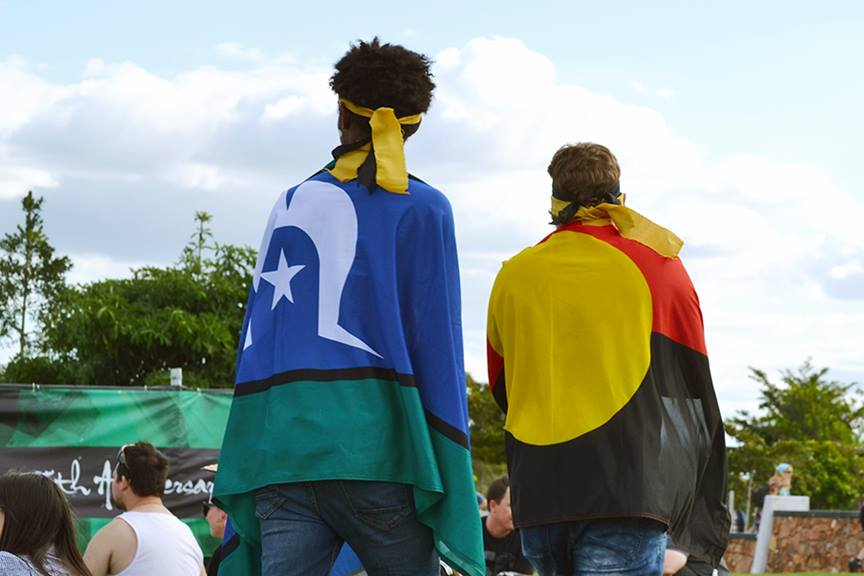 two guys walking side by side one wearing the aboriginal flag and other wearing torres strait island