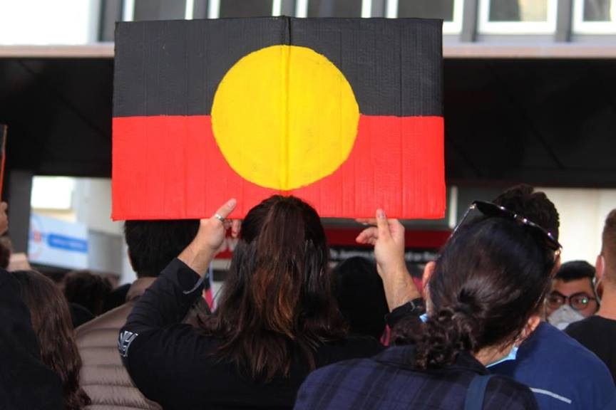 Yound woman holding Aboriginal flag