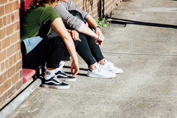2 girls sitting on the sidewalk talking